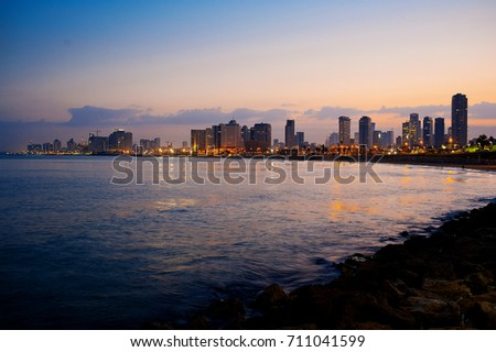 Dawn in Tel Aviv. View of the sea, beach and buildings.