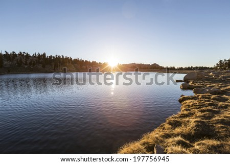 Dawn light at Cirque Lake in California's Inyo National Forest. - stock photo