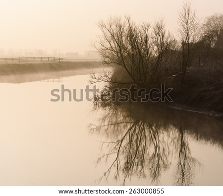 Dawn mists shroud a tranquil River Parrett on the Somerset Levels - stock photo