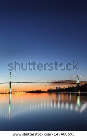 Dawn on a clear morning in Vancouver with the Lion's Gate Bridge crossing to Stanley park and reflecting in Burrard Inlet. The office towers of downtown Vancouver rise in the back ground.  - stock photo