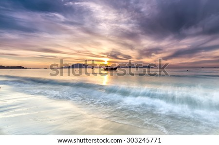 Dawn on Doc Let beach with the waves pounding the shore in the distance is small boat first welcome sunshine greet the new day. - stock photo