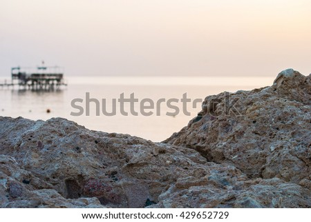 Dawn on the stone island and pier on the abstract sea background - stock photo