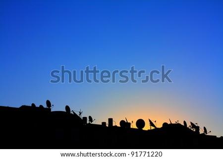 Dawn over satellite aerial - stock photo