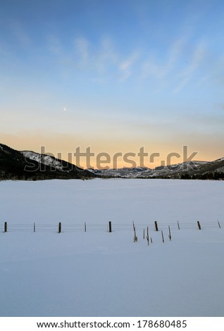 Dawn sky above a fence in rural Utah, USA. - stock photo