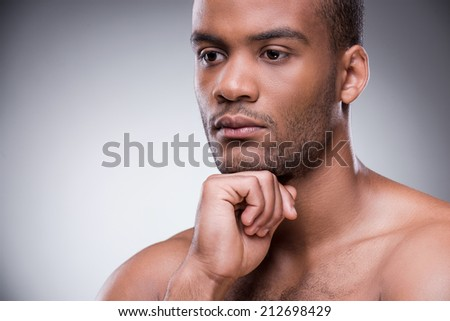 Day dreamer. Portrait of young African man holding hand on chin and looking away while standing against black background - stock photo