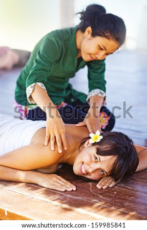 day in beach spa, bali (focus on the eyes of woman who is being massaged) - stock photo