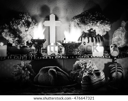 Day of the dead altar scene with pan de muerto and candles with sad mood lighting. Festivity celebrated throughout Mexico in October 31, November 1 and November 2