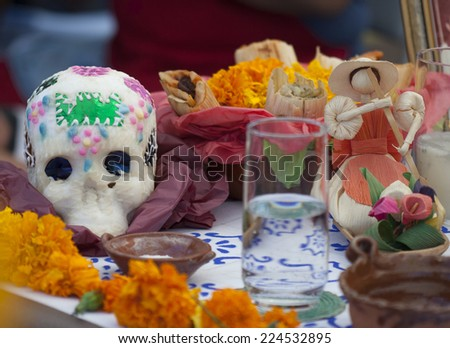 Day of the Dead celebration table with marigolds, sugar skull, and food - stock photo