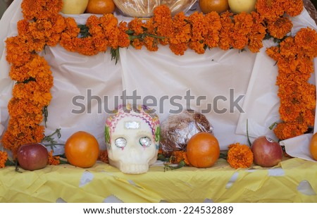 Day of the Dead celebration table with sugar skull, marigolds and oranges - stock photo