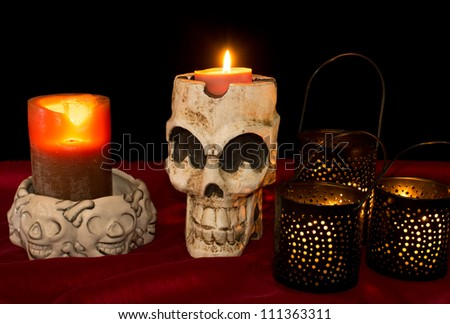 Day of The Dead (Dia de los Muertos) skull with flickering lighted candles - stock photo