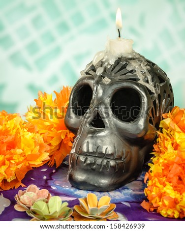 Day of the dead Oaxacan black clay Skull with candle - stock photo