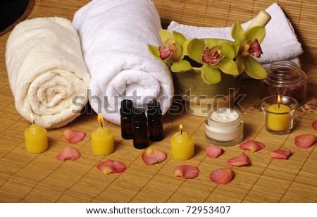 Day spa setting with candles and flowers - stock photo
