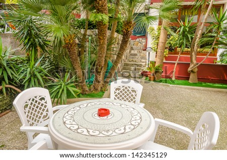 Day view of a hotel exterior with chairs and tents. - stock photo