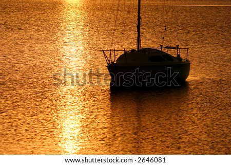 Daybreak with golden light spilling over the water. - stock photo