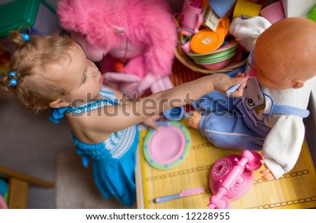 Daycare - baby girl plays with a toy - stock photo