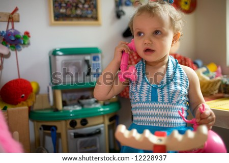 Daycare - baby girl talking by toy phone