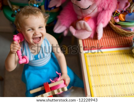 Daycare - baby girl talking by toy phone - stock photo