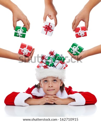 Daydreaming about christmas - pensive boy with presents in his santa hat, isolated - stock photo