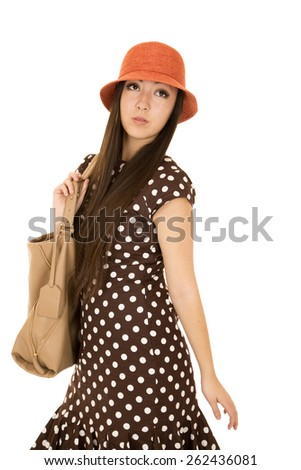 Daydreaming teen model wearing brown polka dots - stock photo