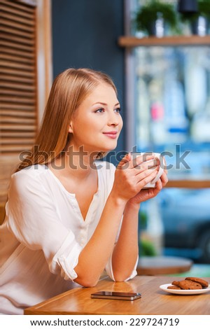 Daydreaming with cup of fresh coffee. Side view of beautiful young smiling woman enjoying coffee in cafe  - stock photo