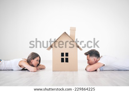 Daydreaming young couple at home - stock photo
