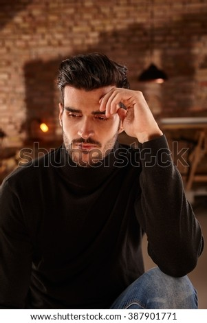 Daydreaming young man sitting at home, thinking, looking down. - stock photo