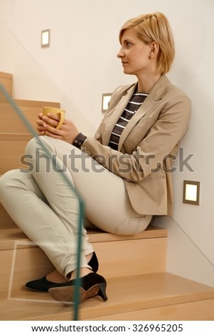 Daydreaming young woman sitting in stairway, drinking tea. Full-length. - stock photo