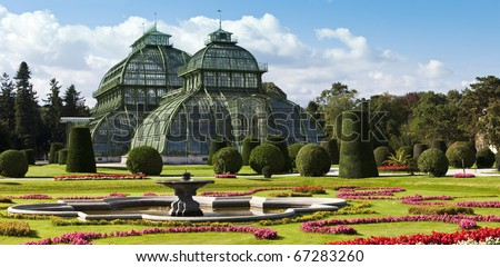 Daylight image of the famous Palmenhaus ( palm house or greenhouse) at the imperial garden of Schoenbrunn of Vienna - Austria - stock photo