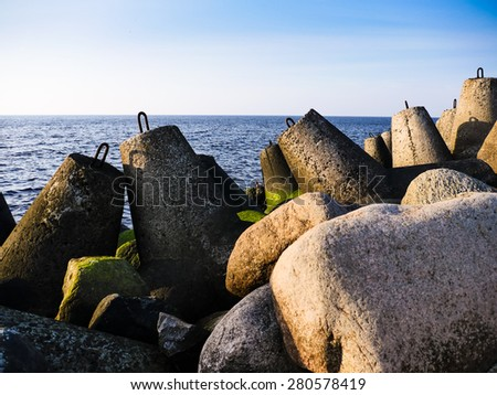 Daylight on the coast of the Riga Gulf at dawn with rocks in foreground - stock photo