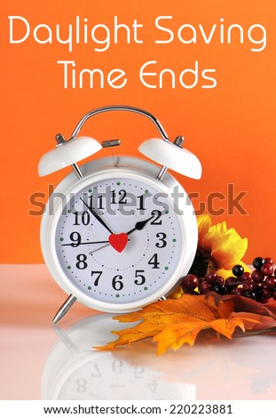 Daylight savings time ends in autumn fall with clock concept and text message on orange background. - stock photo