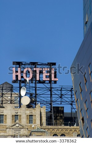 Daytime image of a neon hotel sign against a blue sky on top of building - stock photo