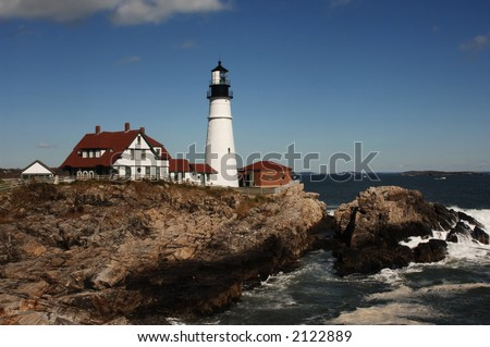Daytime shot of Portland Head lighthouse with bluffs and Atlantic Ocean