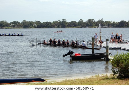 "DAYTONA BEACH, FL - JULY 24:  Racing shells gather around the launching dock at  the ""Halifax Rowing Association's Summer Regatta 2010"" on July 24, 2010 in Daytona Beach, Florida. - stock photo"