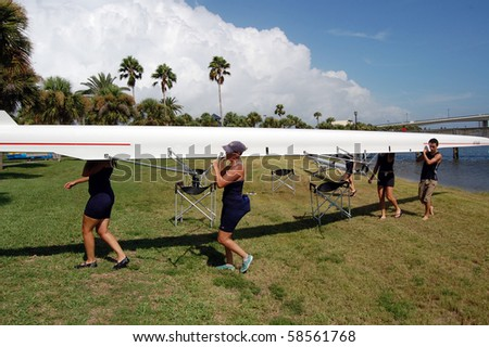 "DAYTONA BEACH, FL - JULY 24:  Rowers shoulder the racing shell during the  ""Halifax Rowing Association's Summer Regatta 2010"" on July 24, 2010 in Daytona Beach, Florida. - stock photo"