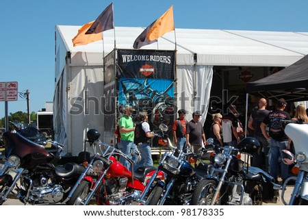 "DAYTONA BEACH, FL - MARCH 17: Bikers check out the vendors downtown during ""Bike Week 2012"" in Daytona Beach, Florida. March 17, 2012"