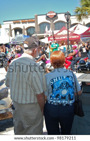 "DAYTONA BEACH, FL - MARCH 17:  Spectators of all ages watch the bikers cruise Main Street during ""Bike Week 2012"" in Daytona Beach, Florida. March 17, 2012"