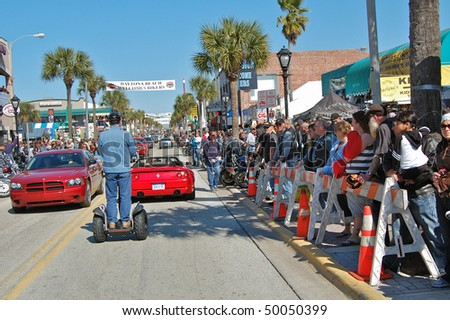 "DAYTONA BEACH, FL - MARCH 6:  Spectators watch all types of vehicles cruise down Main Street amid the sea of bikers in town for ""Bike Week 2010"" in Daytona Beach, Florida. - stock photo"