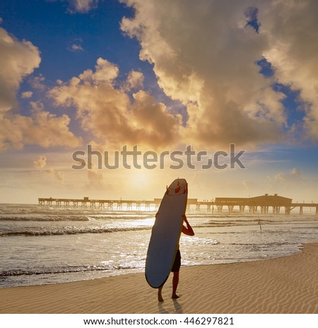Daytona Beach in Florida shore with pier and unknown surfer walking USA - stock photo