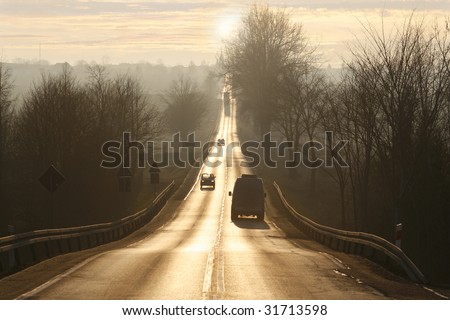 dazzling sunset before narrow road, go away for good, linear perspective in the middle of the public road, go into the unknown - stock photo