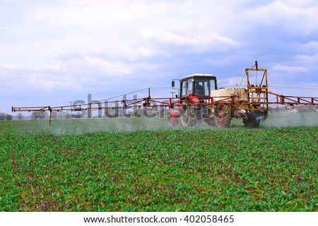 dding  chemical weed and pest killers on a spring field with the plantlet of rape - stock photo