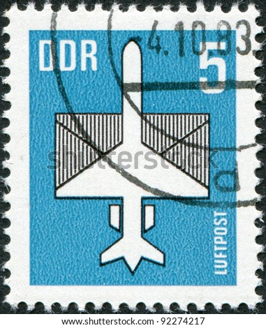 DDR - CIRCA 1983: A stamp printed in DDR, shows a stylized airplane with an envelope, circa 1983 - stock photo