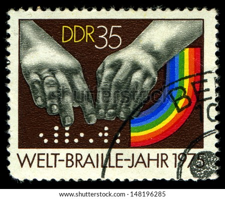 DDR- CIRCA 1975: A stamp printed in DDR, shows  hands reading a font of Braille , circa 1975 - stock photo