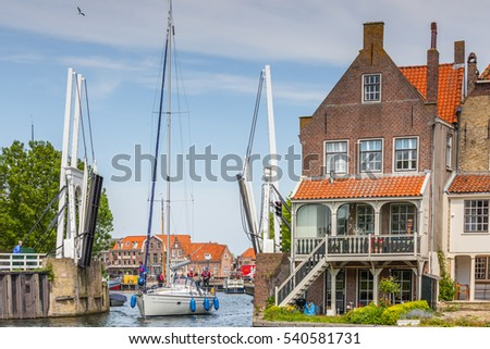 De Bocht, Enkhuizen, North Holland, Netherlands, may 31, 2013: Rear facades of the houses on the bend with open drawbridge and sailing boat