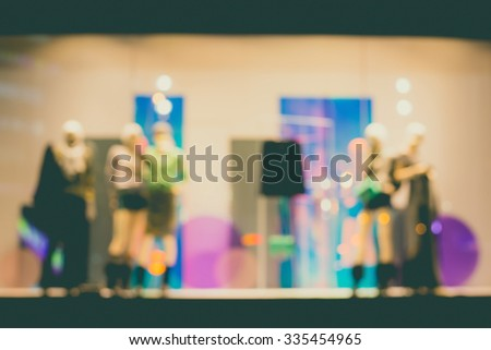 De focused/Blur image of boutique window with dressed mannequins. Boutique display window with mannequins in fashionable dresses. Toned image. - stock photo