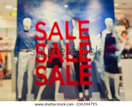 """De focused/Blur image of boutique window with dressed mannequins. Boutique display window with mannequins in fashionable dresses. Words """"sale"""" on boutique display window.  - stock photo"""