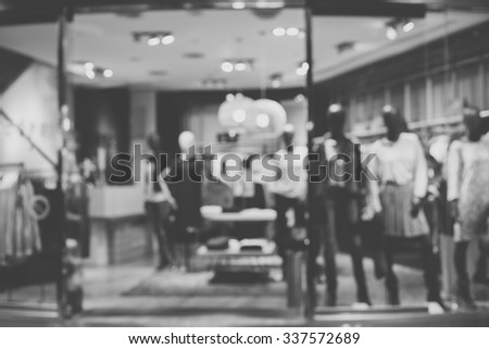 De focused/Blur image of boutique window with dressed mannequins. Boutique display window with mannequins in fashionable dresses. Black and white image. - stock photo