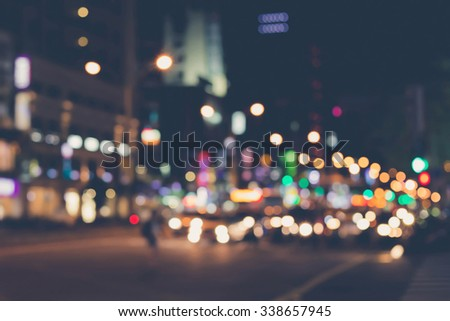 De focused/blur image of city at night. A man crossing the road. De focused, blurred urban abstract traffic background. - stock photo