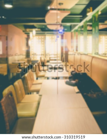 De focused/Blurred image of a girl who is tired and falls asleep in cafe.