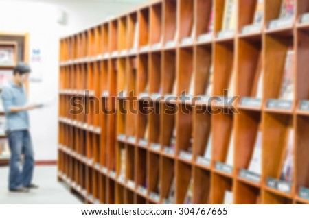 De focused/Blurred image of a man reading a magazine before magazine stand in library. Library background. - stock photo