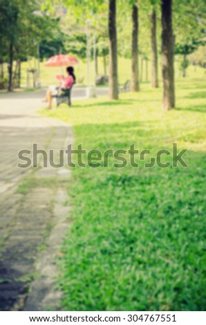 De focused/Blurred image of a woman sitting on park bench, holding a red umbrella and a red fan in her hand. Retro effect.